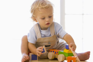 baby-indoors-playing-with-toy-truck
