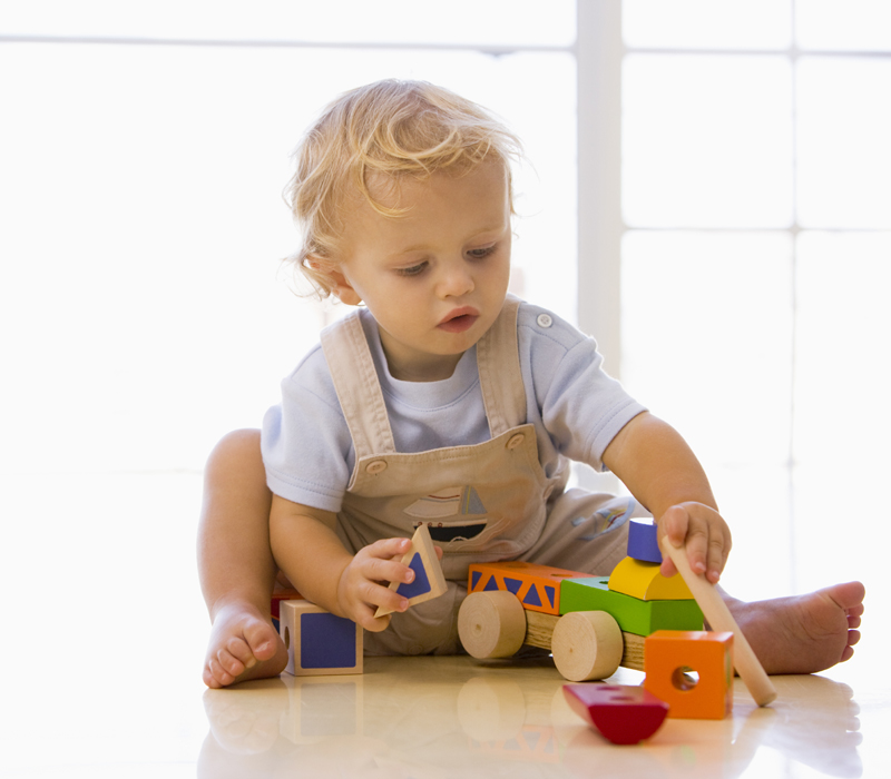 Cute baby playing with his American made wooden toy truck