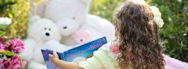 Little girl reading to her teddybears