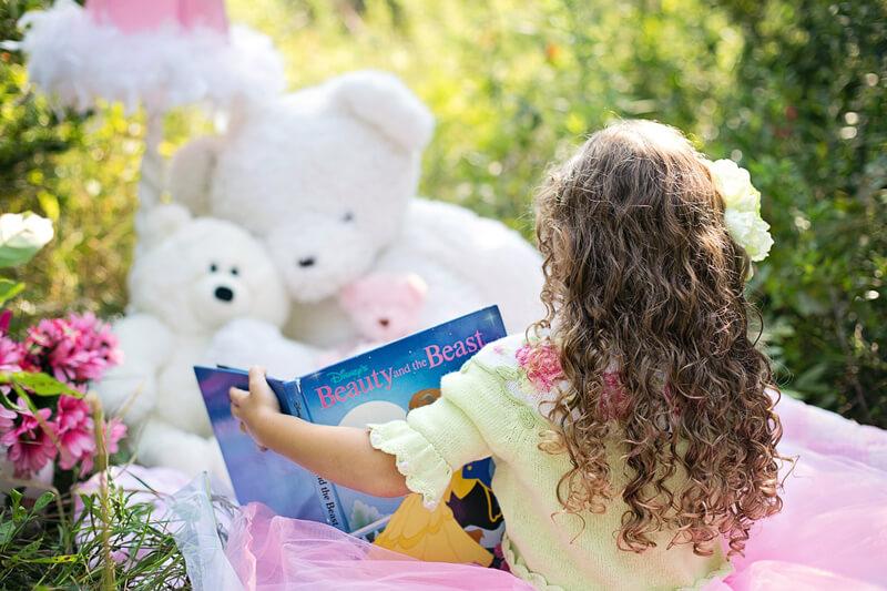 Little girl reading to her teddy bears
