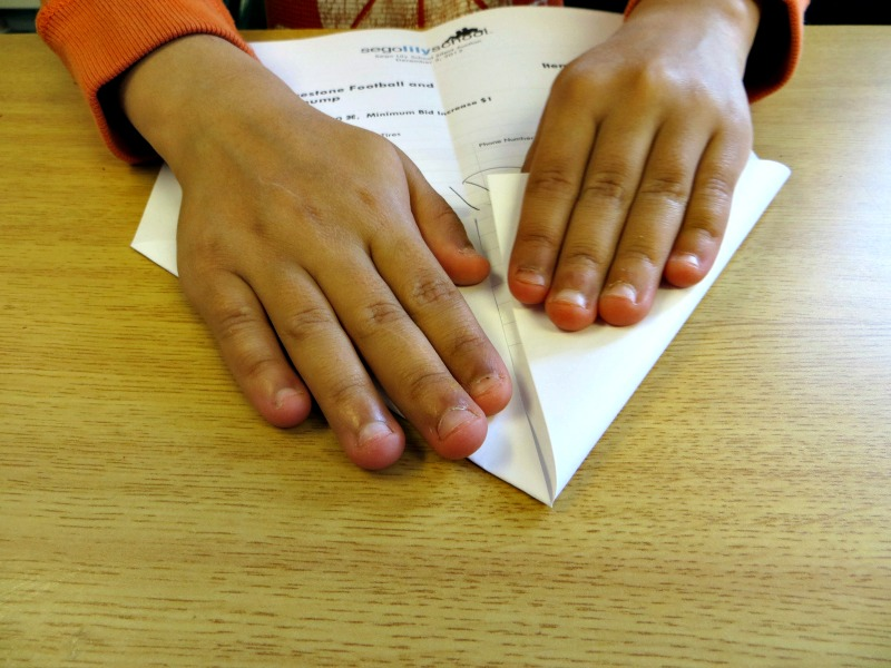 Young child making a paper airplane